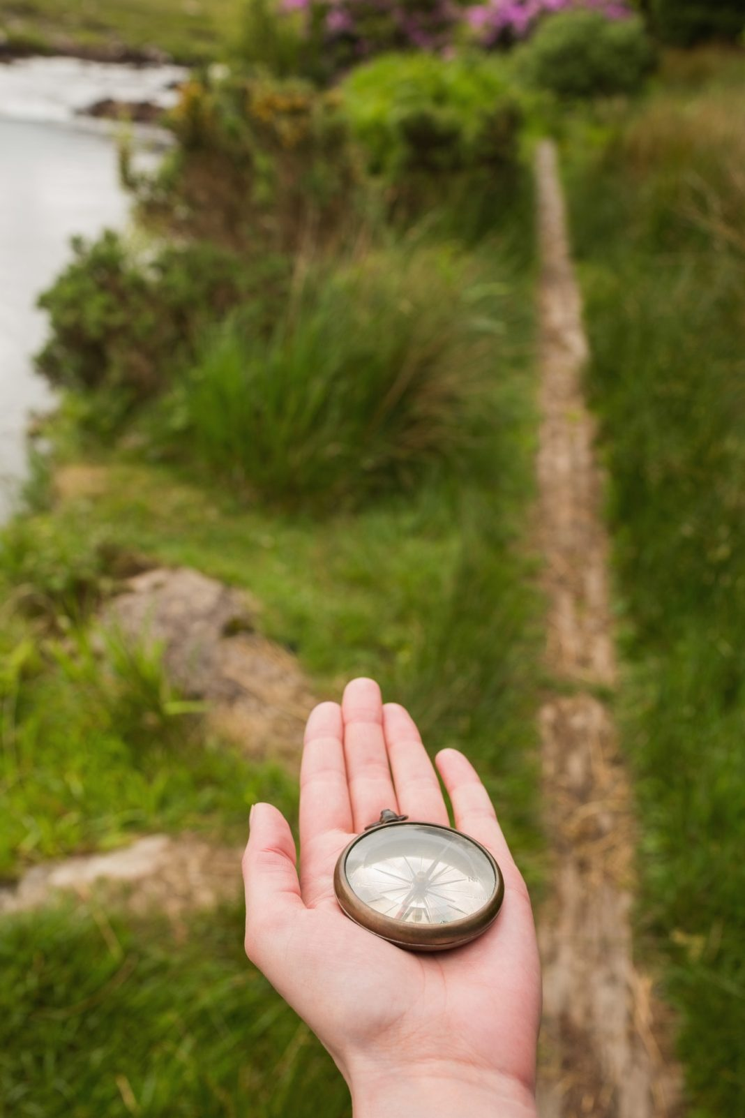 Hand holding old fashioned compass showing the way on a country trail